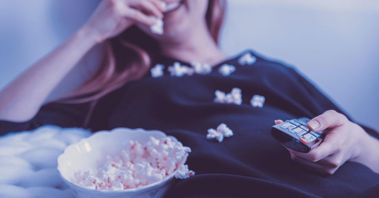 Una chica come palomitas mientras ve el cine en casa